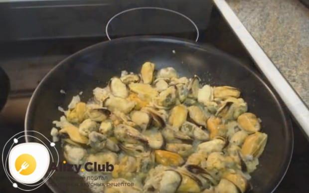 Выкладываем мидии на сковороду к луку.
