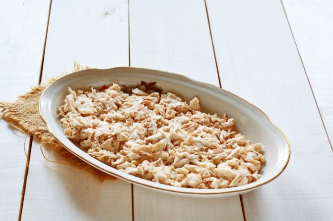 Выложите кусочки варёного куриного филе