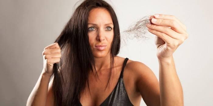 Женщина держит в руке клок волос