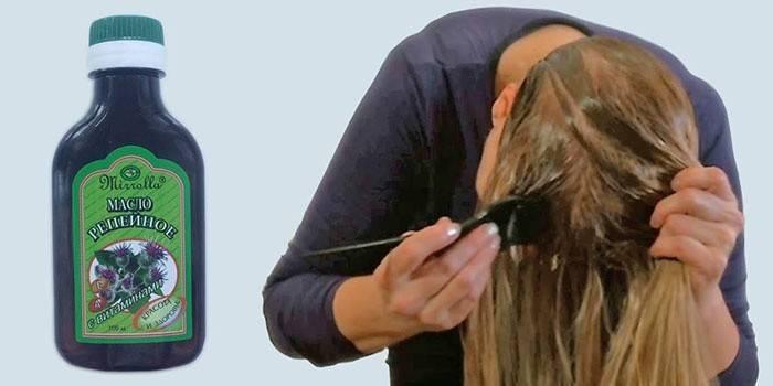 Женщина наносит на волосы репейное масло