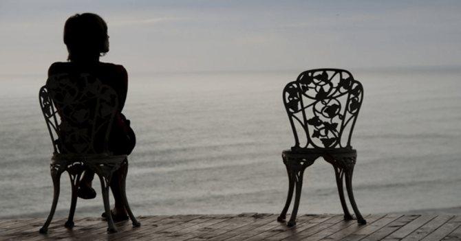 Женщина сидит одна у моря.