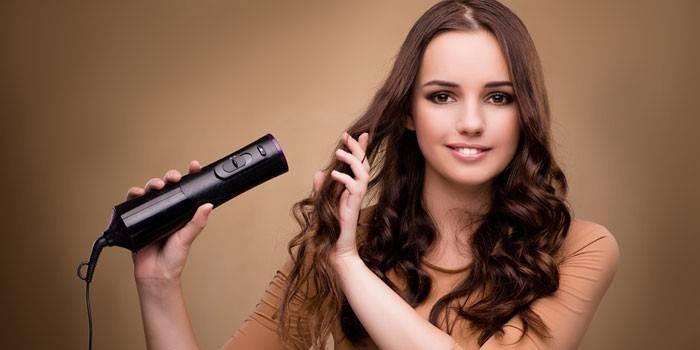 Женщина сушит волосы феном
