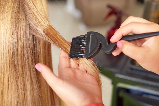 Женщине наносят косметическое средство на волосы; уход за волосами зимой