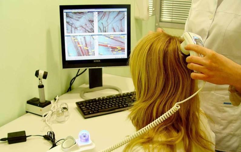 Женщину обследуют с помощью трихоскопа